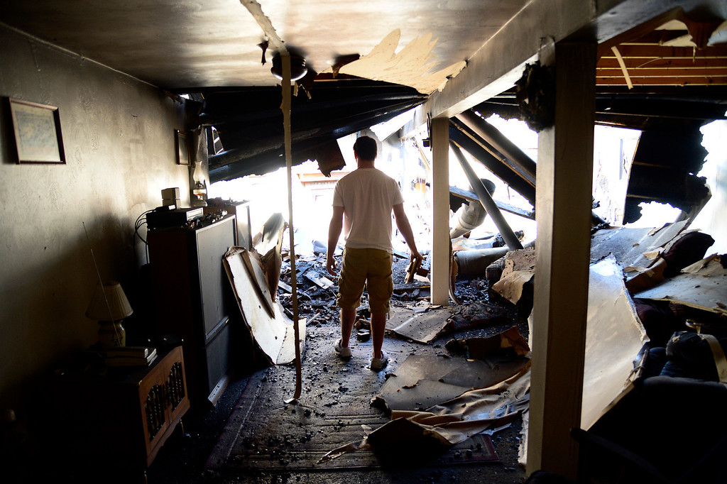 . Eric Fruits walks through the basement of what remains of his grandfather\'s home looking for pictures and knick knacks that survived. Mahala Gaylord, The Denver Post
