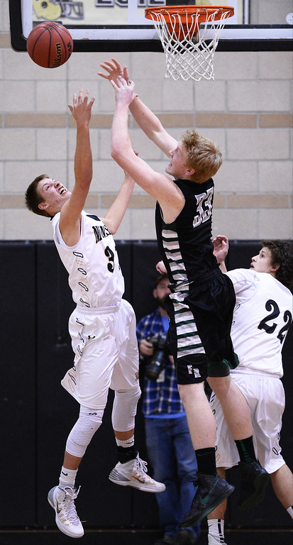 . Matt Laine of Fossil Ridge High School (55) and Ben Beauchamp of Monarch High School (31) are fighting for the control of the free ball  in the 2nd half of the game at Monarch High School Gym.  (Photo by Hyoung Chang/The Denver Post)