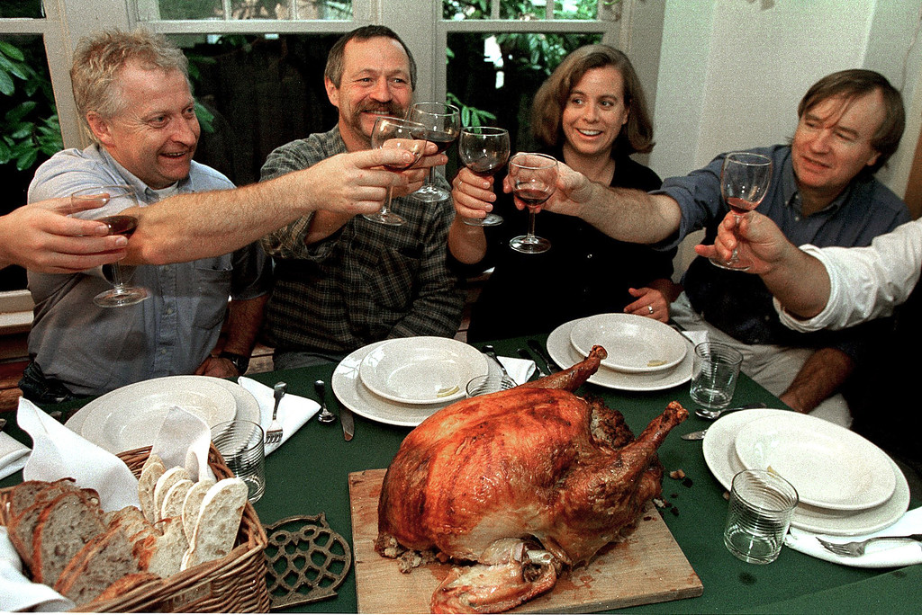 . French agriculture activist Jose Bove (2nd L) begins a traditional U.S. Thanksgiving Day turkey dinner with a toast at the house of Deanna Notaro (2nd R) in Seattle, WA 25 November.  DAN LEVINE/AFP/Getty Images