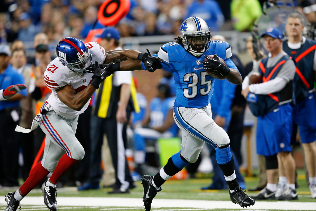 . New York Giants free safety Ryan Mundy (21) reaches for Detroit Lions running back Joique Bell (35) during the second quarter of an NFL football game in Detroit, Sunday, Dec. 22, 2013. (AP Photo/Rick Osentoski)