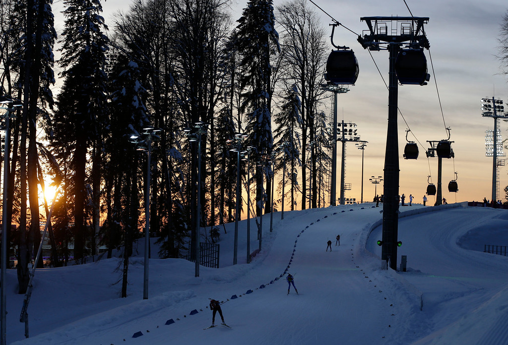 . Athletes compete as the sun sets during the mixed biathlon relay at the 2014 Winter Olympics, Wednesday, Feb. 19, 2014, in Krasnaya Polyana, Russia. (AP Photo/Felipe Dana)