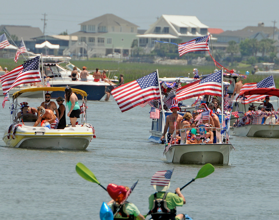 . Boaters take part in the 31st annual Fourth of July Boat Parade, Friday, July 4, 2014, in Murrells Inlet, S.C. (AP Photo/The Sun News, Charles Slate)