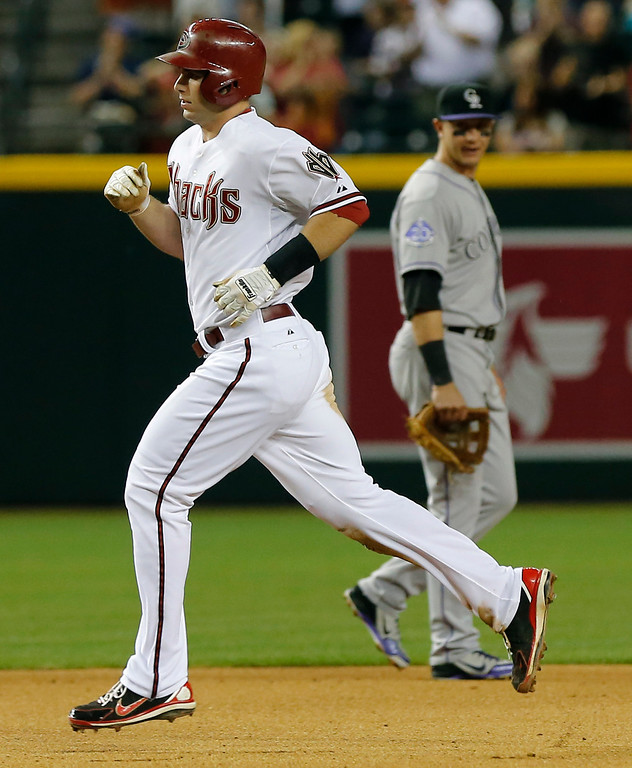 . Arizona Diamondbacks\' Paul Goldschmidt rounds the bases as Colorado Rockies\' Troy Tulowitzki looks on during the fourth inning of a baseball game, Thursday, April 25, 2013, in Phoenix. (AP Photo/Matt York)