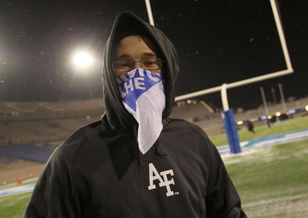 . Tyler Albright, a member of the Air Force cheer squad, bundles up as cold temeperatures and a light snow envelop Falcon Stadium before Air Force hosts UNLV in the first quarter of an NCAA football game at Air Force Academy, Colo., on Thursday, Nov. 21, 2013. (AP Photo/David Zalubowski)
