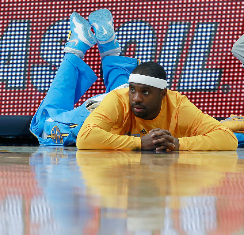 . Denver Nuggets guard Ty Lawson, who has been sidelined because of a broken rib, looks on from the sidelines in the fourth quarter of an NBA basketball game in Denver, Tuesday, Feb. 25, 2014. Portland won 100-95. (AP Photo/David Zalubowski)