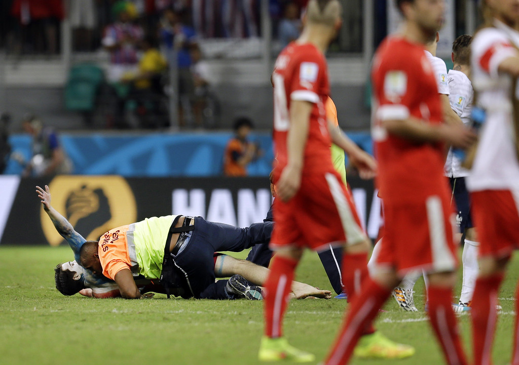 . A spectator is taken down on the pitch by a security guard following Switzerland\'s 5-2 loss to France during the group E World Cup soccer match between Switzerland and France at the Arena Fonte Nova in Salvador, Brazil, Friday, June 20, 2014. (AP Photo/Natacha Pisarenko)