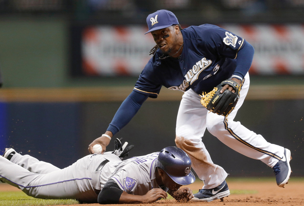 . Milwaukee Brewers\' Rickie Weeks, right, tags out Colorado Rockies\' Chris Nelson during the second inning of a baseball game Tuesday, April 2, 2013, in Milwaukee. (AP Photo/Jeffrey Phelps)