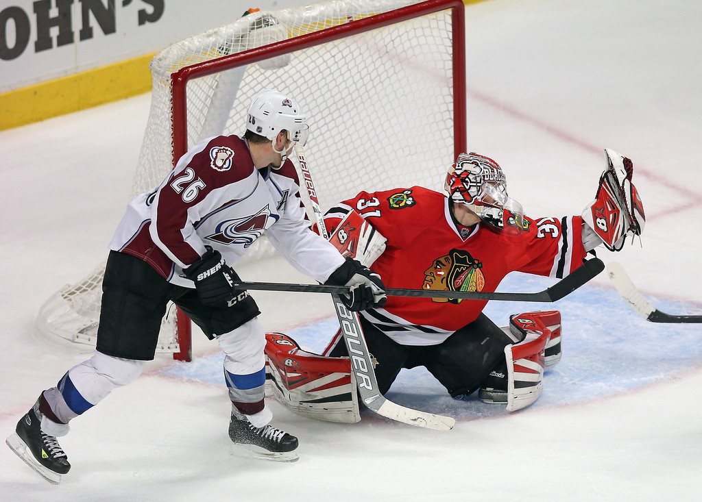. CHICAGO, IL - DECEMBER 27: Antti Raanta #31 of the Chicago Blackhawks makes a glove save next to Paul Stastny #26 of the Colorado Avalanche at the United Center on December 27, 2013 in Chicago, Illinois.  The Blackhawks defeated the Avalanche 7-2. (Photo by Jonathan Daniel/Getty Images)