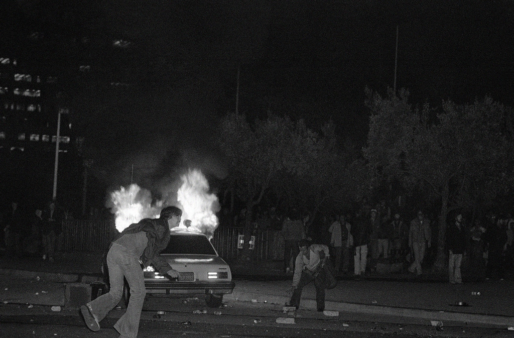 . As demonstrators reach for rocks, a San Francisco police car goes up in flames as some 5,000 persons rioted following return of verdict in the Dan White trial, May 22, 1979.  White was convicted of manslaughter in the slayings of Mayor George Moscone and Supervisor Harvey Milk.  (AP Photo/Paul Sakuma)