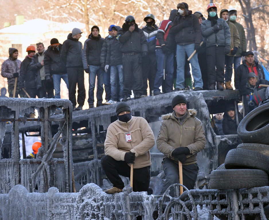 . Activists of Euromaidan (the name given for Independence square) stand in front of a barricade to prevent a police attack in Kiev on January 24, 2014. Anti-government protesters were today occupying regional administration buildings in six regions in western Ukraine after storming the buildings, in a major new challenge for President Viktor Yanukovych. (SERGEI SUPINSKY/AFP/Getty Images)
