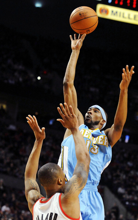. Denver Nuggets small forward Corey Brewer (13) shoots the ball over Portland Trail Blazers point guard Damian Lillard (0) during the first quarter of their NBA basketball game in Portland, Oregon, February 27, 2013.  REUTERS/Steve Dykes