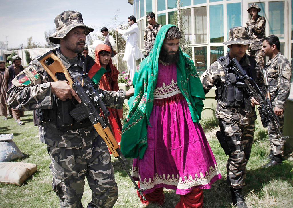 . In this March 28, 2012 file photo, Afghan security forces escort Taliban militants clad in Afghan women dresses to be presented to the media at the Afghan intelligence department in Mehterlam, Laghman province, east of Kabul, Afghanistan.  Afghan Intelligence forces arrested seven Taliban militants in Qarghayi district of Laghman province. (AP Photo/Rahmat Gul, File)