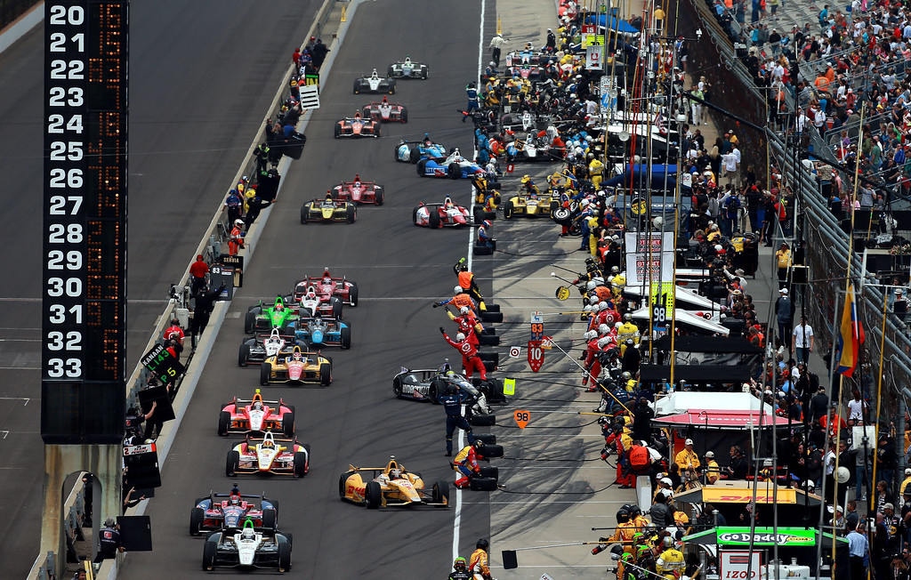 . Cars pull in and out of their pit boxes during the IZOD IndyCar Series 97th running of the Indianapolis 500 mile race at the Indianapolis Motor Speedway on May 26, 2013 in Indianapolis, Indiana.  (Photo by Jonathan Ferrey/Getty Images)