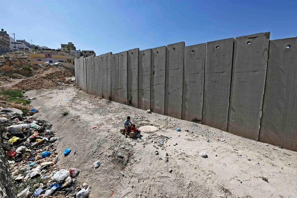 . A Palestinian boy plays near a section of the controversial Israeli barrier in Shuafat refugee camp in the West Bank near Jerusalem July 29, 2013. Israeli and Palestinian officials put forward clashing formats for peace talks due to resume in Washington on Monday for the first time in nearly three years after intense U.S. mediation. It is unclear how the United States hopes to bridge the core issues in the dispute, including borders, the future of Jewish settlements on the West Bank, the fate of Palestinian refugees and the status of Jerusalem. REUTERS/Ammar Awad
