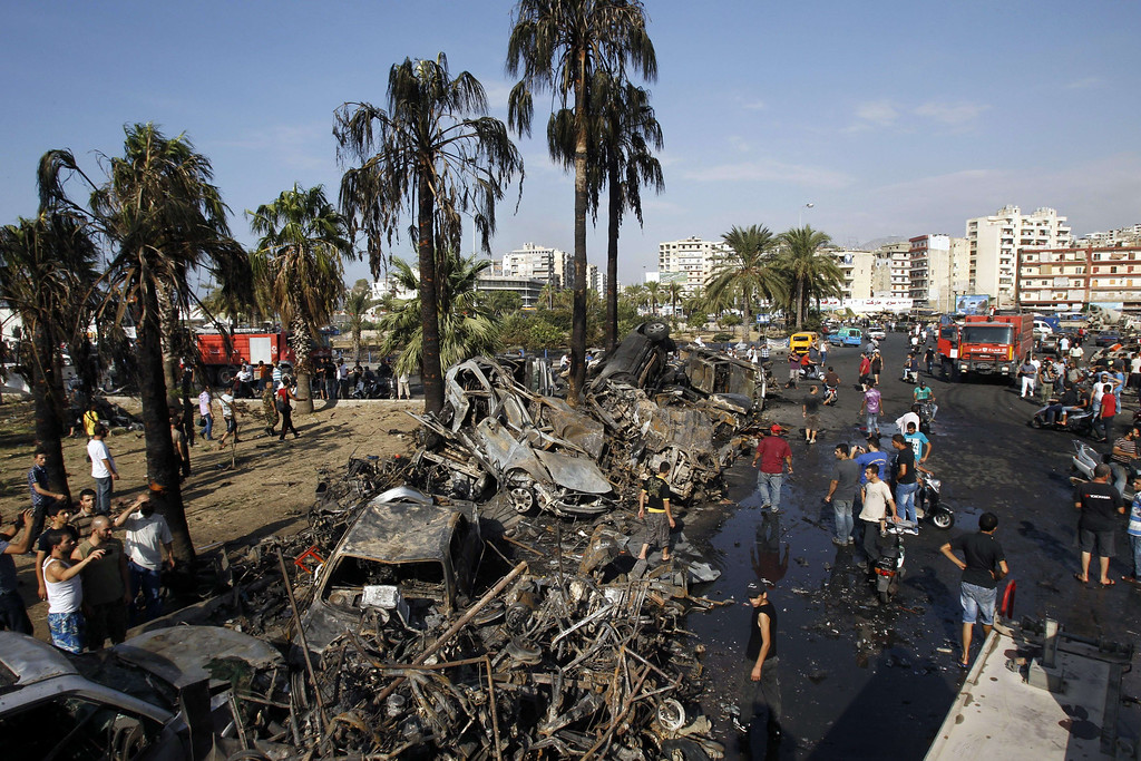 . Lebanese civilians gather next to the site of a blast outside the Al-Taqwamosque in the northern city of Tripoli on August 23, 2013.  AFP PHOTO/ANWAR AMROANWAR AMRO/AFP/Getty Images
