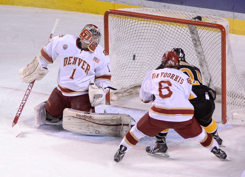 . DENVER, CO. - FEBRUARY 21, 2014: Tigers\' right wing Jared Hanson (24) got past Denver defenseman Matt Vanvoorhis (6) to put the puck past goalie Sam Brittain (1) in the first period. The University of Denver hockey team hosted Colorado College at Magness Arena Friday night, February 21, 2014. Photo By Karl Gehring/The Denver Post