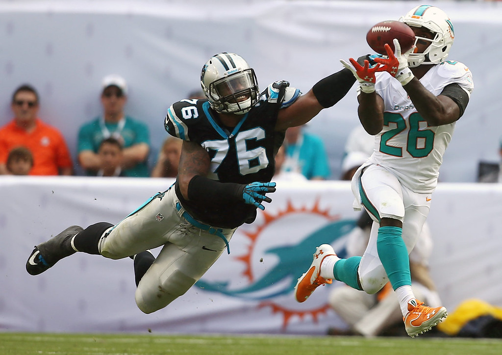 . Miami Dolphins running back Lamar Miller (26) grabs a pass as Carolina Panthers defensive end Greg Hardy (76) applies pressure during the first half of an NFL football game on Sunday, Nov. 24, 2013, in Miami Gardens, Fla. (AP Photo/J Pat Carter)