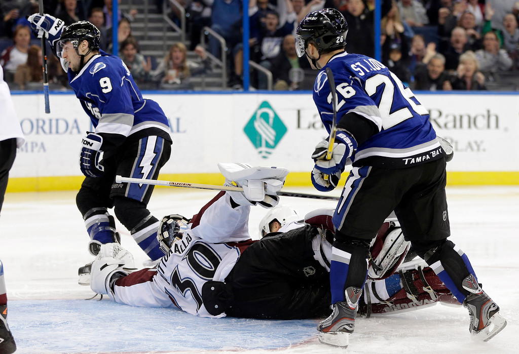 . Tampa Bay Lightning center Tyler Johnson (9) celebrates after scoring past Colorado Avalanche goalie Sami Aittokallio (30), of Finland, during the second period of an NHL hockey game Saturday, Jan. 25, 2014, in Tampa, Fla. Looking on is Lightning\'s Martin St. Louis (26). (AP Photo/Chris O\'Meara)