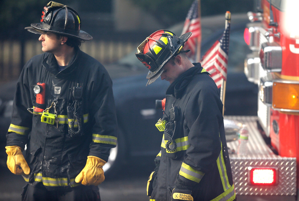 . A firefighter, right, lowers his head at the scene of a multi-alarm fire at a four-story brownstone in the Back Bay neighborhood near the Charles River, Wednesday, March 26, 2014, in Boston. (AP Photo/Steven Senne)