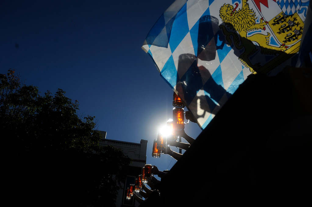 . DENVER, CO: Sept 28, 2013  Contestants raise their steins during the Stein Hoisting competition as the Bavarian Flag waives from the stage. The contestants held their steins in front of them for as long as they could manage.   (Photo By Erin Hull/The Denver Post)