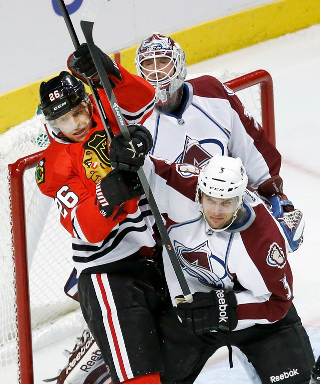 . Colorado Avalanche defenseman Nate Guenin (5) and Chicago Blackhawks center Michal Handzus battle in front of goalie Jean-Sebastien Giguere during the first period of an NHL hockey game Friday, Dec. 27, 2013, in Chicago. (AP Photo/Charles Rex Arbogast)