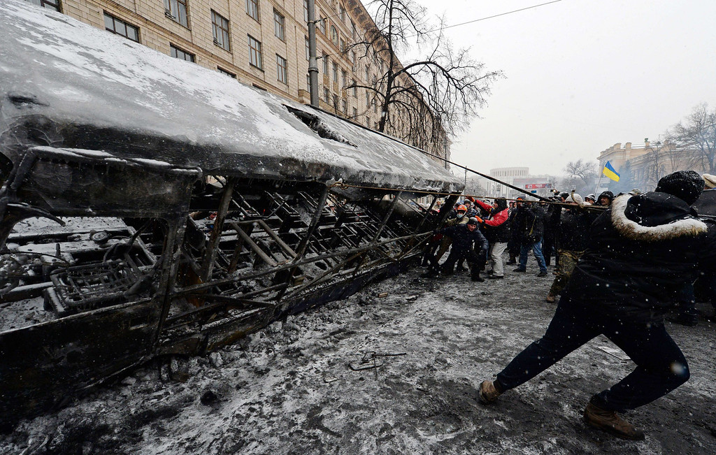 . Ukrainian opposition activists build barricades with burned bus after violent clashes in central Kiev January 21, 2014. Ukrainian protesters and security forces on Tuesday refrained from using further force after two days of clashes but an uneasy standoff remained with neither side giving way. After a night of violence, a temporary truce appeared to be in place with the protesters no longer launching the Molotov cocktails and stones that had marked their action since the clashes erupted on the night of January 19. AFP PHOTO / VASILY  MAXIMOV/AFP/Getty Images