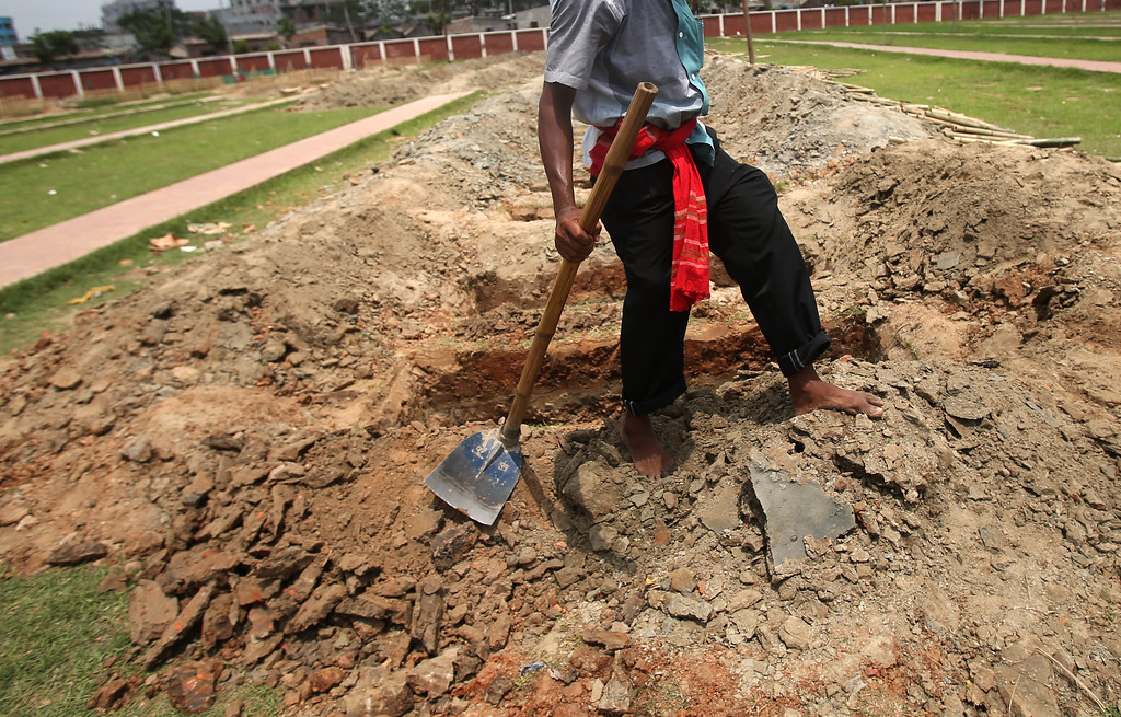 . A worker leaves after digging one of many graves at a cemetery where unclaimed bodies are buried, in preparation for a mass burial for victims of the garment factory building that collapsed, Wednesday, May 1, 2013, in Dhaka, Bangladesh.  (AP Photo/Wong Maye-E)