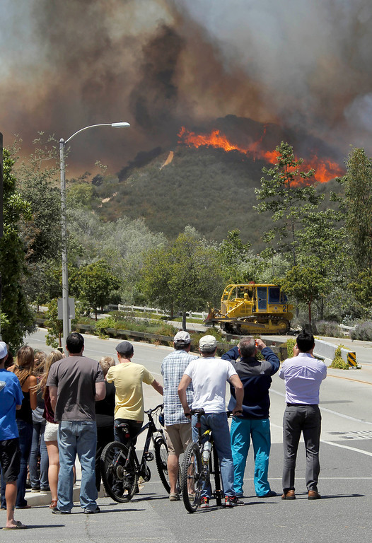 . Residents watch as a wildfire burns on a hill near Thousand Oaks, Calif. on Thursday, May 2, 2013.  (AP Photo/Nick Ut)