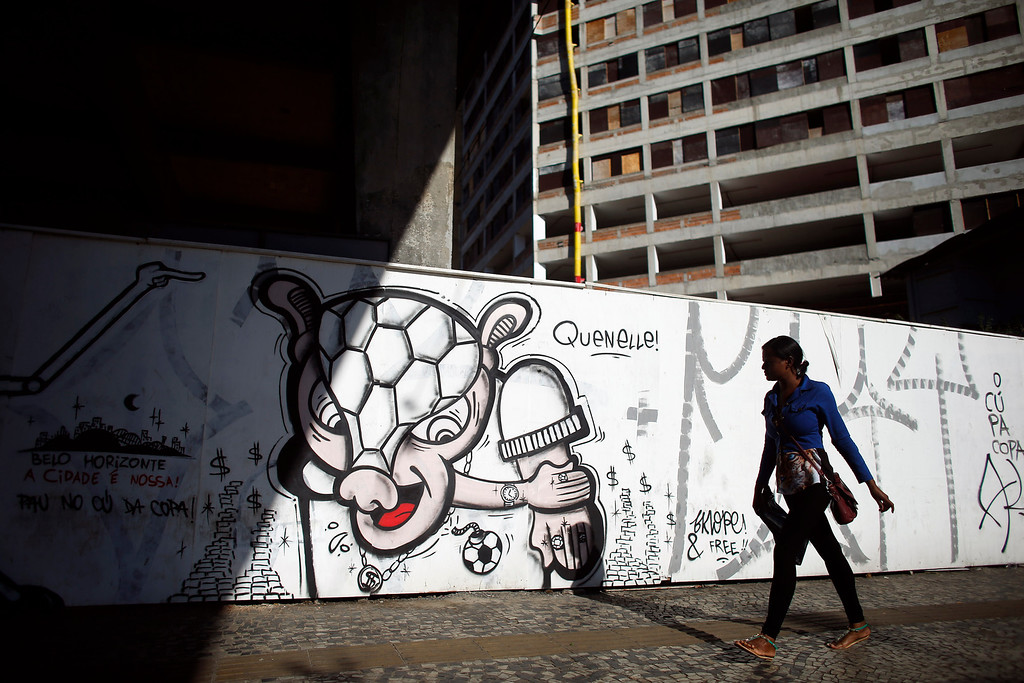 """. A woman walks by a mural depicting the World Cup mascot \""""Fuleco\"""" stealing money in Belo Horizonte, Brazil, Tuesday, June 10, 2014. There have been steady anti-government protests across Brazil blasting spending on the World Cup which starts June 12 and demanding improvements in woeful public services. (AP Photo/Victor R. Caivano)"""