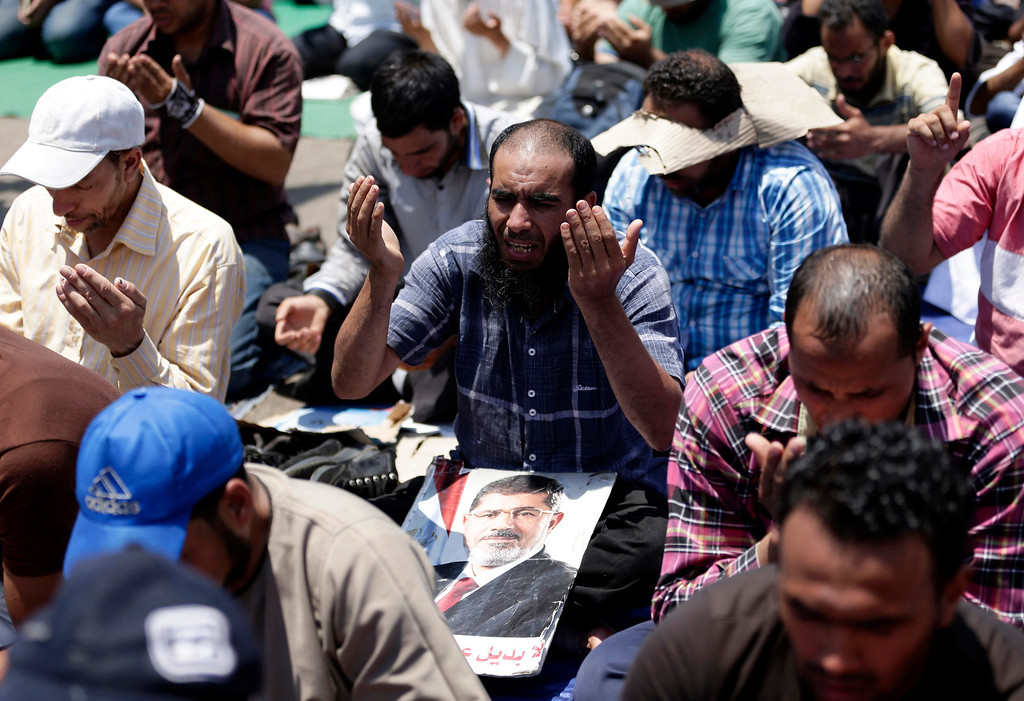 ". Supporter of ousted Egyptian President Mohammed Morsi pray during the Friday prayer before a protest near the University of Cairo, Giza, Egypt, Friday, July 5, 2013. Tens of thousands, mainly Islamists, chanted ""down with military rule\"" in protests around the country Friday, venting their fury at the military for ousting President Mohammed Morsi and vowing to restore him to office. The first major attack by militants, in Sinai, hiked fears that the Islamists\' extreme fringe will turn to violent retaliation for Morsi\'s ouster. (AP Photo/Hassan Ammar)"