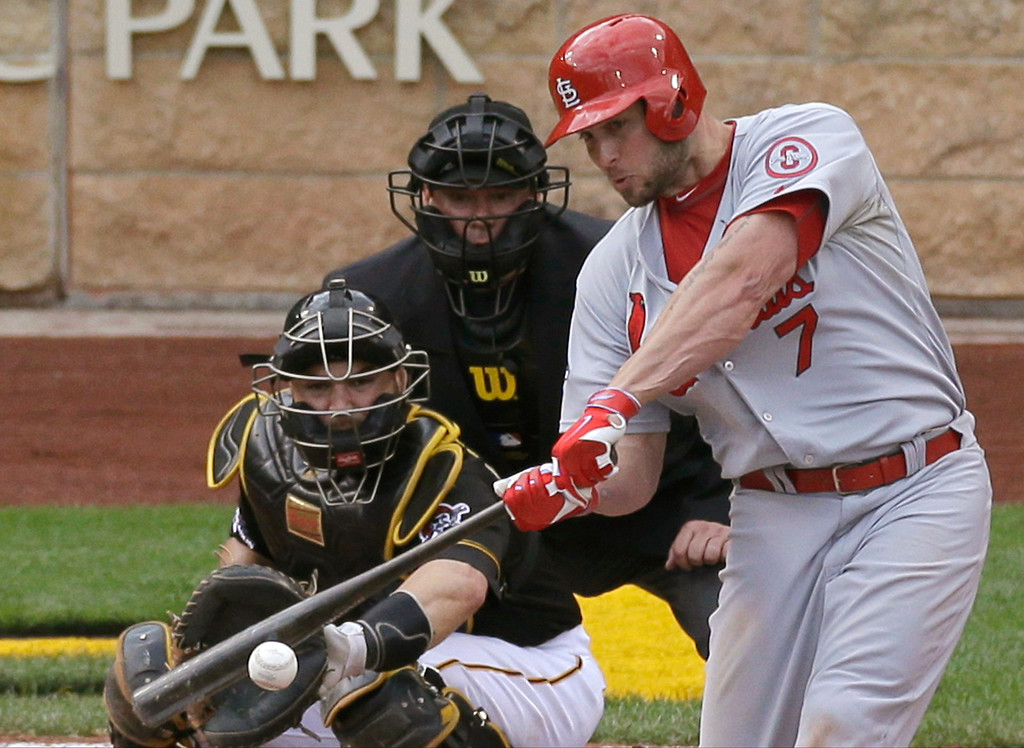 . St. Louis Cardinals\' Matt Holliday (7) hits a two-run home run in front of Pittsburgh Pirates catcher Russell Martin in the sixth inning of Game 4 of a National League baseball division series, Monday, Oct. 7, 2013, in, Pittsburgh. (AP Photo/Tom Puskar)
