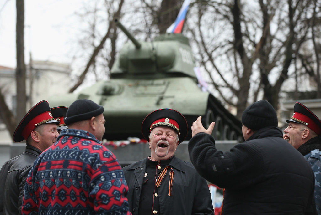 . Pro-Russian Cossacks share a laugh next to a war monument at a gathering of pro-Russian supporters outside the Crimean parliament building on February 28, 2014 in Simferopol, Ukraine. According to media reports Russian soldiers have occupied the airport at nearby Sevastapol while soldiers whose identity could not be initially confirmed have stationed themselves at Simferopol International Airport in moves that are raising tensions between Russia and the new Kiev government. Crimea has a majority Russian population and armed, pro-Russian groups have occupied government buildings in Simferopol.  (Photo by Sean Gallup/Getty Images)