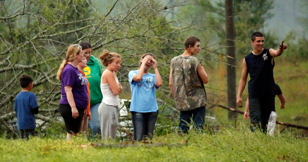 . Residents of Four Corners look at the damage left by a tornado that hit their small community about 20 miles from Louisville, Monday, April 28, 2014. Tornados flattened homes and businesses, flipped trucks over on highways and injured numerous  people in Mississippi and Alabama on Monday as a massive, dangerous storm system passed over several states in the South, threatening additional twisters as well as severe thunderstorms, damaging hail and flash floods. (AP Photo/Rogelio V. Solis)