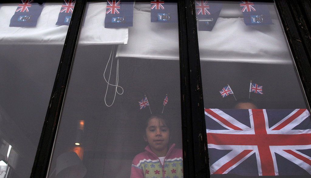 . A girl with Union Jack flags on her head watches a parade in Stanley, March 10, 2013. Voters in the remote British-ruled Falkland Islands hold a referendum on their future today that seeks to challenge Argentina\'s increasingly vocal sovereignty claim. REUTERS/Marcos Brindicci
