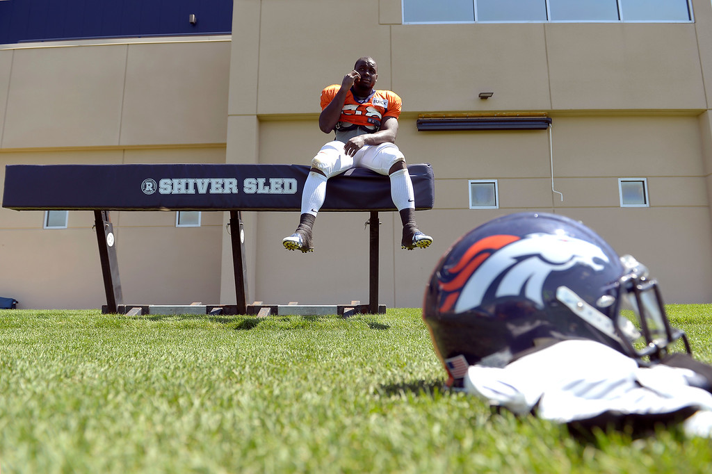 . Denver Broncos running back Montee Ball (38) sits on the sled as he conducts an interview on the phone after practice August 20, 2013 at Dove Valley (Photo by John Leyba/The Denver Post)
