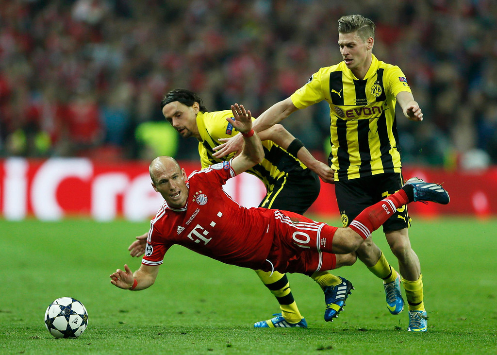 . Bayern Munich\'s Arjen Robben falls under a challenge by Borussia Dortmund\'s Neven Subotic (rear L) and Lukasz Piszczek (R) during their Champions League Final soccer match at Wembley Stadium in London May 25, 2013.     REUTERS/Stefan Wermuth