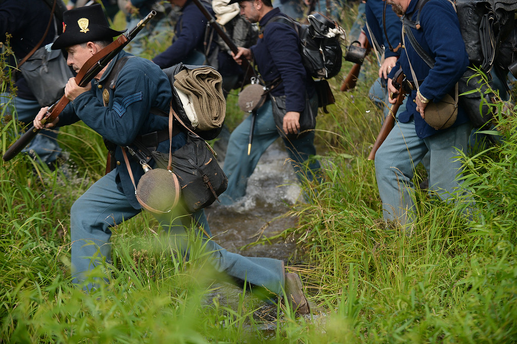 """. The 24th Michigan \""""Iron Brigade\"""" crosses a stream to pursue the Confederates at the Blue-Grey Alliance re-enactment battle held at the Bushey Farm on June 28, 2013. LEBANON DAILY NEWS - JEREMY LONG"""
