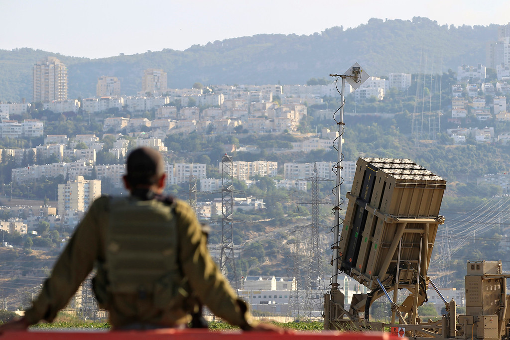 . An Israeli soldier is seen next to an Iron Dome rocket interceptor battery deployed near the northern Israeli city of Haifa, Wednesday, Aug. 28, 2013. Israel ordered a special call-up of reserve troops Wednesday as nervous citizens lined up at gas-mask distribution centers, preparing for possible hostilities with Syria. (AP Photo/Tsafrir Abayov)