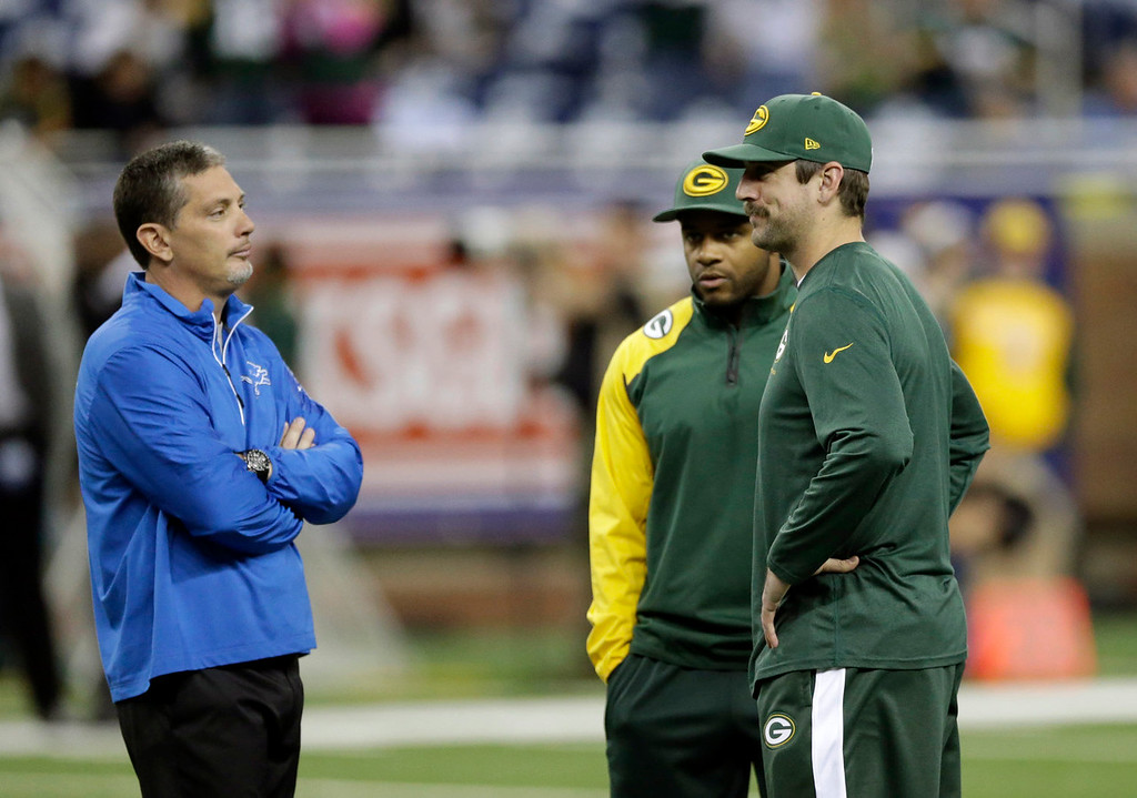 . Detroit Lions head coach Jim Schwartz talks with Green Bay Packers wide receiver Randall Cobb, center, and quarterback Aaron Rodgers during a warm up period before an NFL football game at Ford Field in Detroit, Thursday, Nov. 28, 2013. (AP Photo/Carlos Osorio)