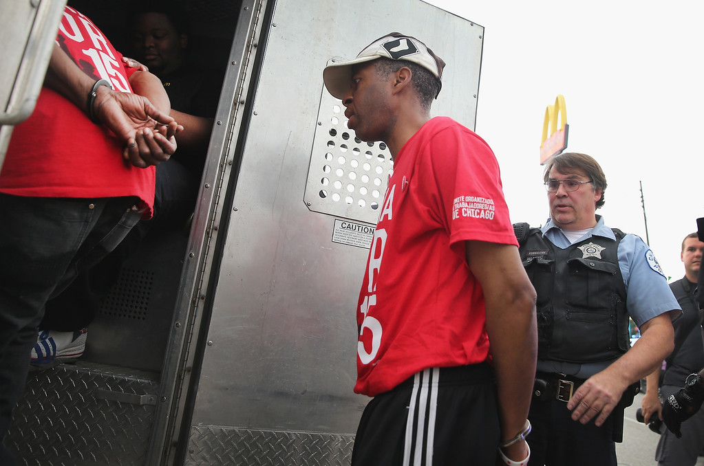 . CHICAGO, IL - SEPTEMBER 04:  Police arrest demonstrators who were protesting for an increase in wages for fast food workers and home care workers after they staged a sit-in on 87th Street during the morning rush hour on September 4, 2014 in Chicago, Illinois. About two dozen protestors were arrested at the demonstration. The demonstration was one of many staged nationwide in a push to increase wages to $15-per-hour for the workers. (Photo by Scott Olson/Getty Images)