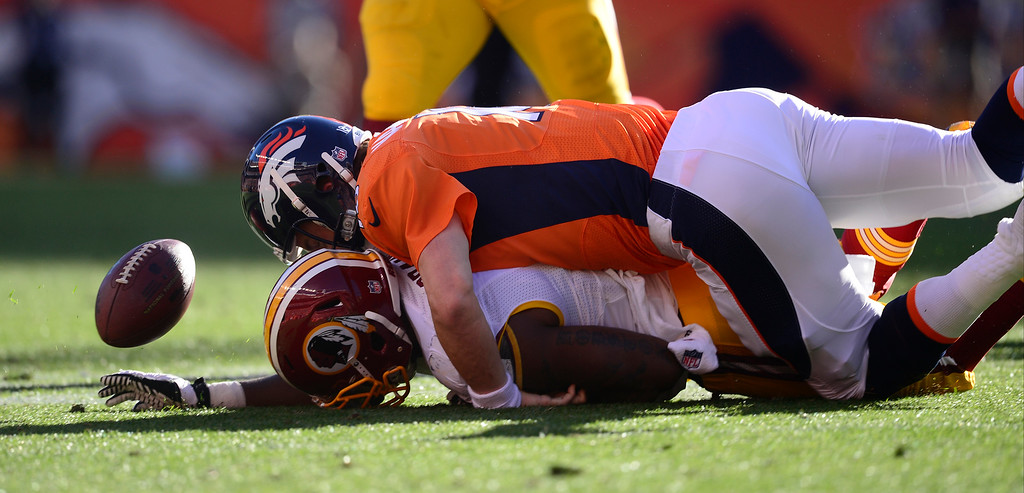 . Denver Broncos quarterback Peyton Manning (18) tackles Washington Redskins outside linebacker Brian Orakpo (98). Manning was trying to prevent Orakpo from recovering his fumble.  (Photo by AAron Ontiveroz/The Denver Post)