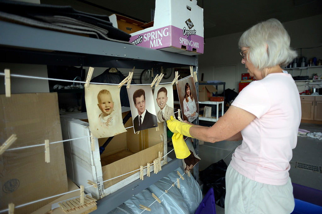 . Nancy Martin hangs old photos of her husband Frank that she managed to salvage September 22, 2013 that were in her basement that was flooded by the rushing water. Nancy and her husband were in Steamboat Springs when there house was flooded. (Photo by John Leyba/The Denver Post)