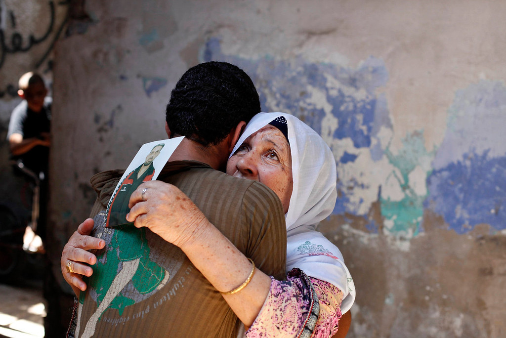 . The mother of Palestinian Ateya Abu Moussa, who has been held prisoner by Israel for 20 years, reacts as she is hugged by her grandson after hearing news on the possible release of her son, in Khan Younis in the southern Gaza Strip July 28, 2013. Abu Moussa was expected to be among more than 100 Arab prisoners to be released as a step to renew stalled peace talks with the Palestinians ahead of plans to convene negotiators in Washington later this week.  Israeli ministers have yet to vote on the releases. REUTERS/Ibraheem Abu Mustafa