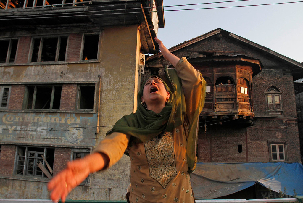 . A Kashmiri woman reacts after paramilitary troops opened fire on a car when the driver allegedly failed to stop at a police barricade in Srinagar, India, Saturday, Sept. 7, 2013. A protest erupted Saturday after Indian police said they killed two alleged militants and two civilians in the disputed Himalayan territory of Kashmir, while authorities maintained tight security for a classical music concert being staged amid separatist objections. The driver was hospitalized in critical condition. (AP Photo/Mukhtar Khan)