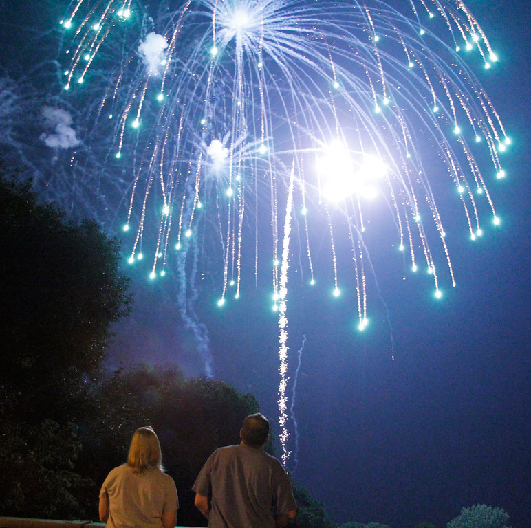 . A pair watch over the bridge as the firework show continues over Riverside Park in West Bend , Wis. on Thursday, July 4, 2013. (AP Photo/The Daily News, John Ehlke)