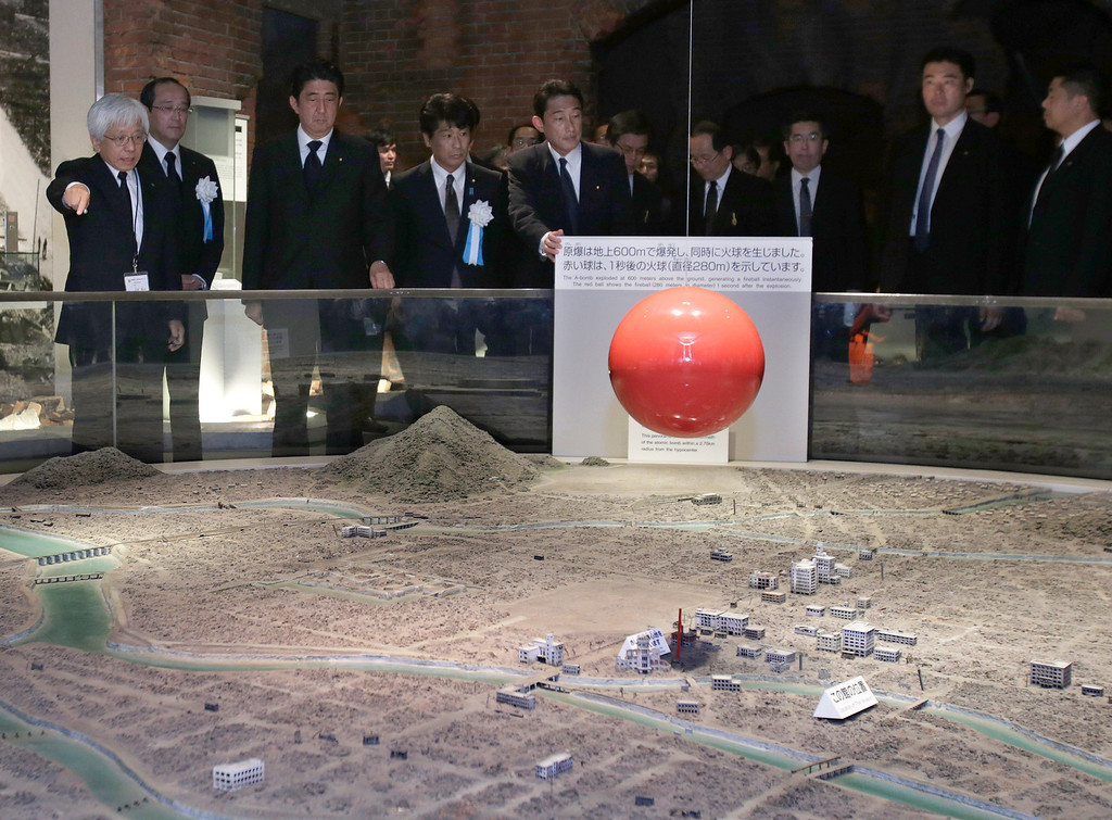 . Japanese Prime Minister Shinzo Abe, third from left, accompanied by Hiroshima Peace Memorial Museum Director Kenji Shiga, left, looks at a diorama of Hiroshima city after the Aug. 6, 1945 atomic bombing, at Hiroshima Peace Memorial Museum in Hiroshima, western Japan, Tuesday, Aug. 6, 2013. (AP Photo/Shizuo Kambayashi)