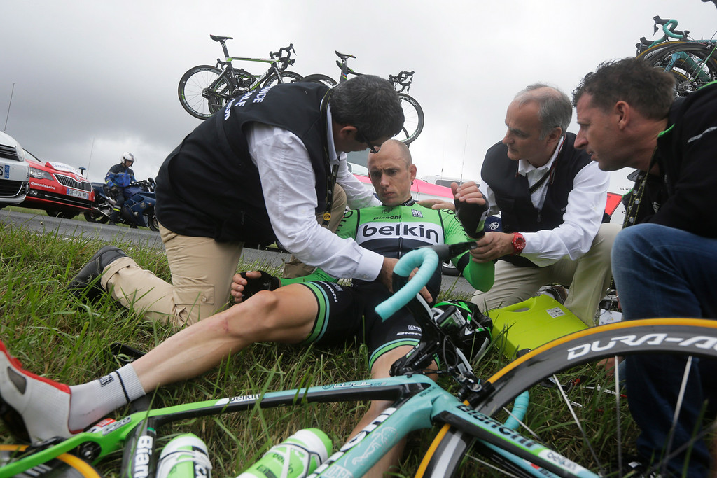 . A Tour de France doctor attends to Netherlands\' Stef Clement after he crashed during the seventh stage of the Tour de France cycling race over 234.5 kilometers (145.7 miles) with start in Epernay and finish in Nancy, France, Friday, July 11, 2014. Clement had to withdraw from the race because of his injuries. (AP Photo/Laurent Cipriani)