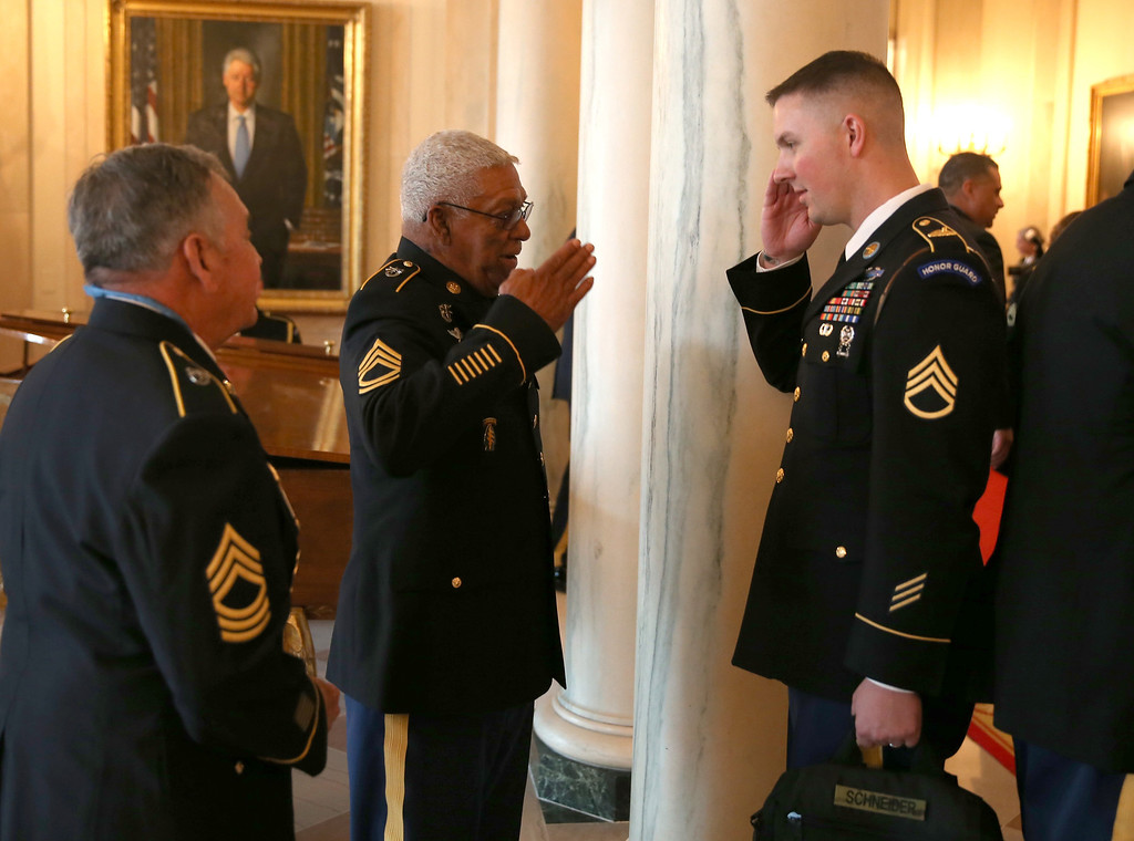 . U.S. Army Staff Sgt. (Ret.) Melvin Morris (L), a Vietnam War veteran, is saluted by U.S. Army Staff Sergeant Christopher Schneider, from U.S. Army Old Guard, 3d U.S. Infantry Regiment, after a ceremony presenting Morris with the Medal of Honor in the White House on March 18, 2014 in Washington, DC.  Melvin Morris, U.S. Army Specialist Four (Ret.) Santiago J. Erevia and U.S. Army Sgt. First Class (Ret.) Jose Rodela were joined by families of 21 others who were presented posthumously with the Medal of Honor for conspicuous gallantry. Following a congressionally mandated review to ensure that eligible recipients were not bypassed due to prejudice the veterans received the Medal of Honor for action during major combat operations in World War II, the Korean War and the Vietnam War.  (Photo by Joe Raedle/Getty Images)