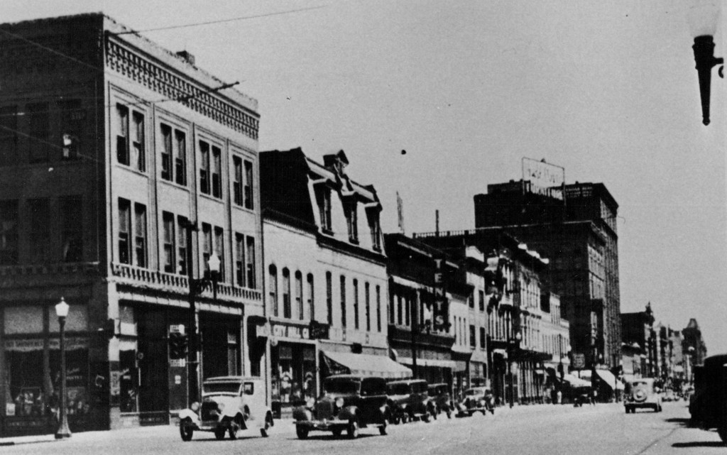 . In this view of the 1401 block of Larimer St. note the corner house with a steeply pitched roof and a second-story balcony on the future site of Gahan\'s Saloon.  Gahan\'s Saloon in 1937 when it returned to hard liquor after prohibition, now restored, still is a bar. (Credit: Colorado Historical Society)