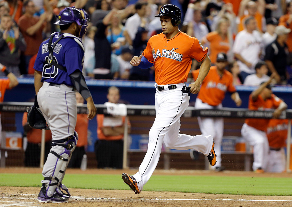 . Miami Marlins\' Giancarlo Stanton, right, runs home to score on a double hit by Casey McGehee as Colorado Rockies catcher Wilin Rosario (20) looks on during the fifth inning of an opening day baseball game, Monday, March 31, 2014, in Miami. (AP Photo/Lynne Sladky)